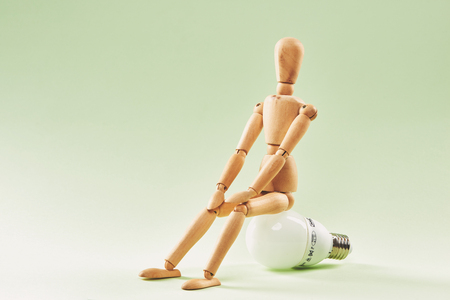 Having no idea. Wood figure mannequin sitting on an incandescent light bulb 版權商用圖片
