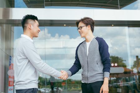 Retrato de socios adultos mediados de éxito dándose la mano, mirando a cámara y sonriendo.