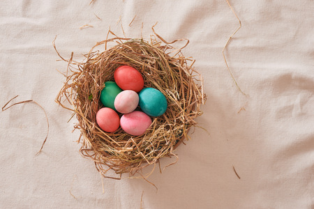 Beautiful Easter multi color egg in straw on wooden background, Easter day concept