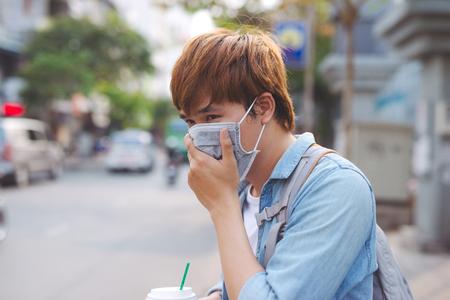 Asiatischer Mann auf der Straße mit Schutzmasken., Kranker Mann mit Grippemaske und Nase in die Serviette als epidemisches Grippekonzept auf der Straße. Standard-Bild