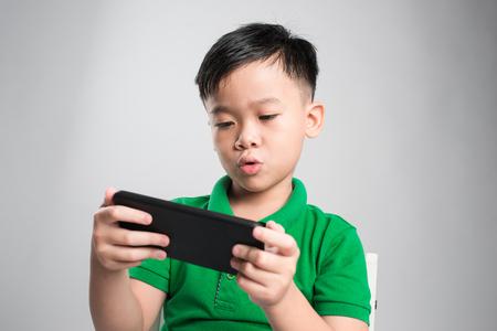 Ritratto di un simpatico ragazzino divertito che gioca su smartphone isolato su sfondo grigio Archivio Fotografico