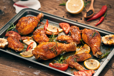 Baked chicken drumstick and wings on baking tray over dark wooden background. Stock fotó