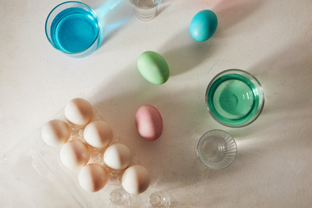 Easter eggs dyeing in glass with colors 写真素材