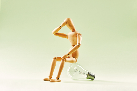 Having no idea. Wood figure mannequin sitting on an incandescent light bulb Banque d'images