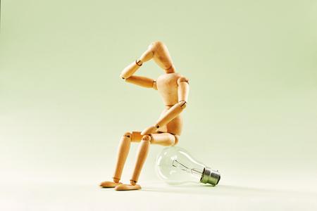 N'ayant aucune idée. Mannequin en bois assis sur une ampoule à incandescence
