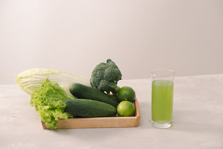 Vegan diet food. Detox drinks. Freshly squeezed juices and smoothies from vegetables. On white background, wooden tray, ingredients. Copy space 写真素材