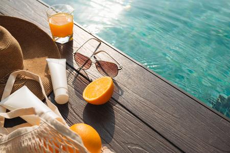Strandhut, Orangensaft und Sonnenbrille in der Nähe des Swimmingpools Standard-Bild