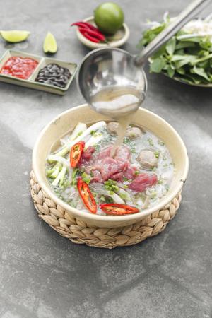 Pho Bo - Vietnamese verse rijstnoedelsoep met rundvlees, kruiden en chili. Voorraad wordt gegoten. Het nationale gerecht van Vietnam. Stockfoto