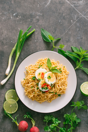 Dry instant noodles put egg with fresh herbs, garnish of cilantro and Asian basil, lemon, lime on dark stone background