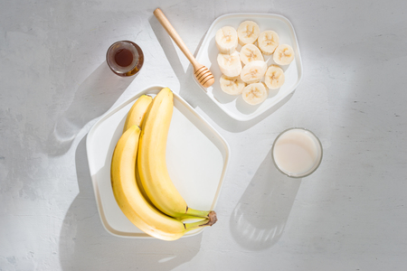 Yummy bananas and bowl with slices on wooden background