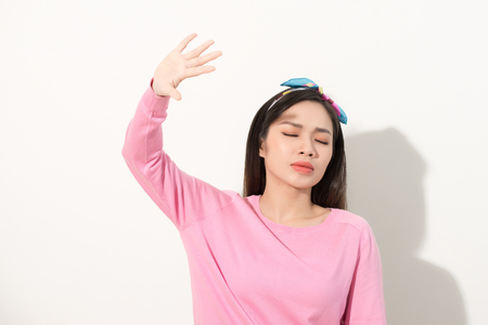 Portrait of a beautiful Asian girl covering face by hand of bright sun light. woman in a pink dress protecting her face from solar light. Skin care or beauty concept