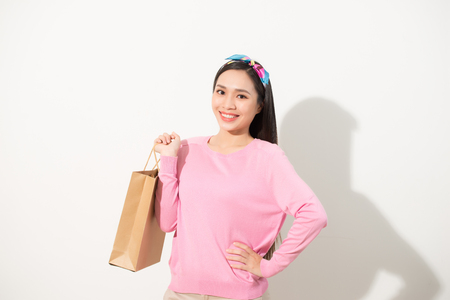 Beautiful young woman (girl) standing and holding a light brown bag, which can be applied to any logo. White background. Portrait in full growth Stock fotó