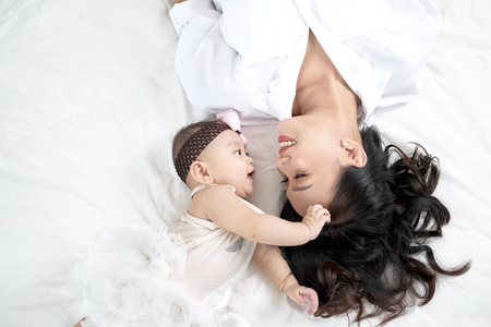 Cute little baby girl and her mother lying on a floor.