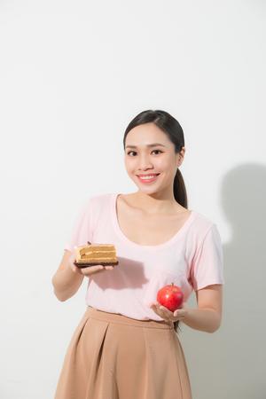 La ragazza in una mano ha una mela, nell'altra una torta.