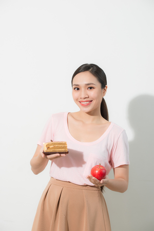 The girl in one hand has an apple, in the other hand a cake.