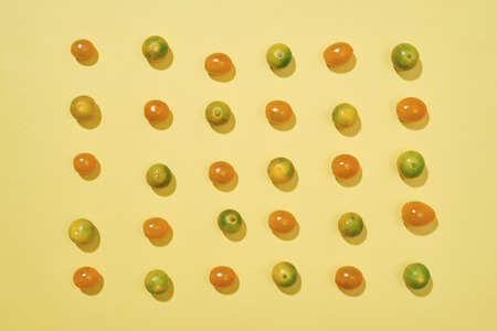 Seamless pattern with tomatoes and Calamondin or citrus microcarpa. Abstract background. Tomato on the yellow background