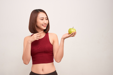 Fitness woman eating apple wearing measuring tape. Fit sporty multicultural Asian / Caucasian female fitness woman isolated on white background. - Image