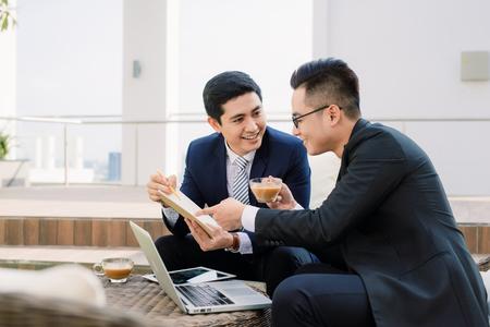 Zwei asiatische Geschäftsleute, die das iPad im Stadtpark verwenden.