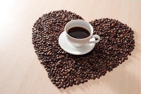La tazza di caffè nel mezzo della forma ama i chicchi di caffè sullo sfondo di legno