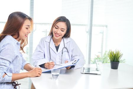 Doctora habla con la paciente en la oficina del hospital mientras escribe en el registro de salud del paciente sobre la mesa. Servicio sanitario y médico.