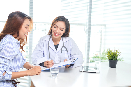 Female doctor talks to female patient in hospital office while writing on the patients health record on the table. Healthcare and medical service. Stockfoto