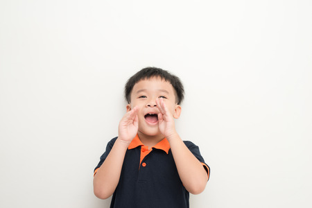 Surprised little boy. Shocked little boy keeping mouth open and touching face with hands while standing isolated on white