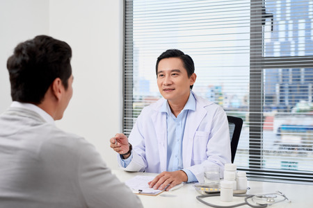 Asian doctor consults young patient Stock Photo