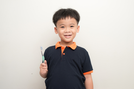 Cheerful little boy holding a tooth brush over white background, Studio portrait of a healthy mixed race boy with a toothbrush isolated Stock Photo - 121990495