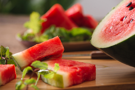 Sliced watermelon on the wood background Imagens