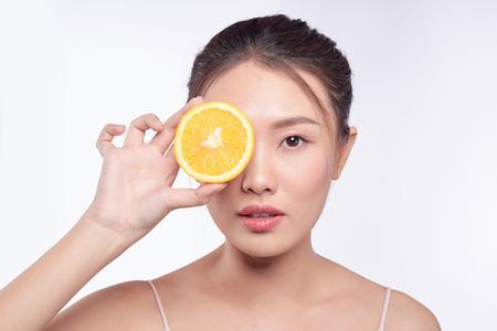 Joven y bella mujer asiática posando con una rodaja de naranja sobre fondo blanco.