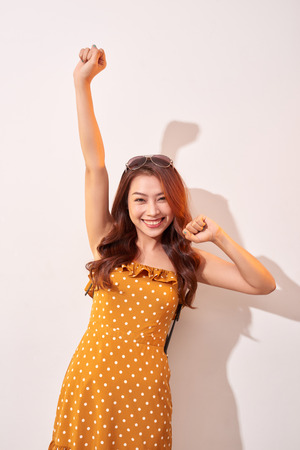 Young beautiful cheerful woman wearing in orange polka dots dress dancing and posing over beige wall. Good mood. Hands up! People Emotions Beauty Fashion Lifestyle concepts