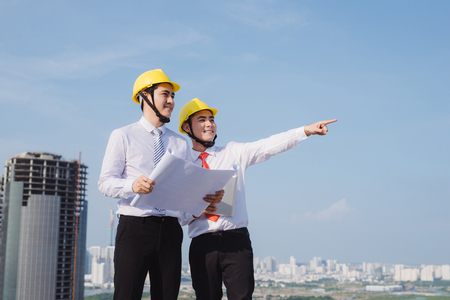 View of a Engineer and worker watching blueprint on construction site Stock Photo
