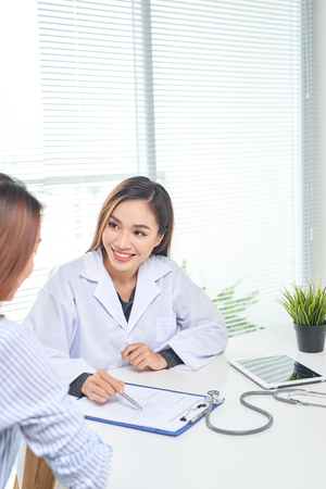 Female doctor talks to female patient in hospital office while writing on the patients health record on the table. Healthcare and medical service. Standard-Bild