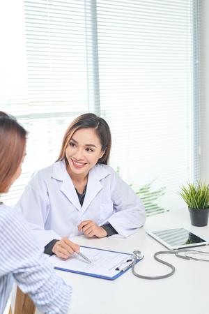 Ärztin spricht mit Patientin im Krankenhausbüro, während sie auf die Patientenakte auf dem Tisch schreibt. Gesundheitswesen und medizinischer Dienst.
