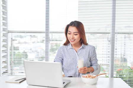 Beautiful young woman sitting at the table in home office, holding glass of milk with cereal, using laptop. 免版税图像 - 121991361