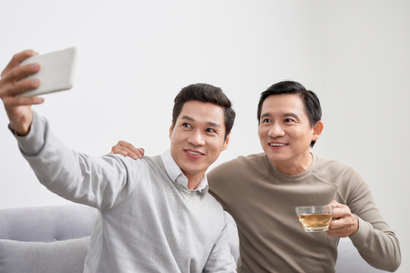 Cheerful young men dressed in casual wear smiling at camera while making selfie photo on front camera Stock Photo
