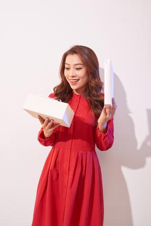 Porträt eines glücklichen lächelnden Mädchens, das eine Geschenkbox lokalisiert auf weißem Hintergrund öffnet