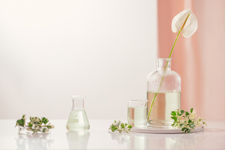 Perfume oils concept. Laboratory glassware with infused floral water on table Stock fotó
