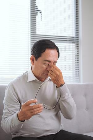 Senior con exceso de trabajo se frota un ojo en fatiga Foto de archivo