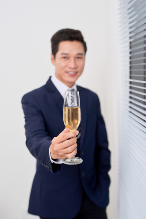 Cheerful businessman giving toast with champagne