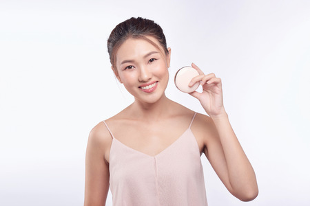 Beautiful asian woman applying powder puff at cheek makeup of cosmetic, beauty of girl with face smile
