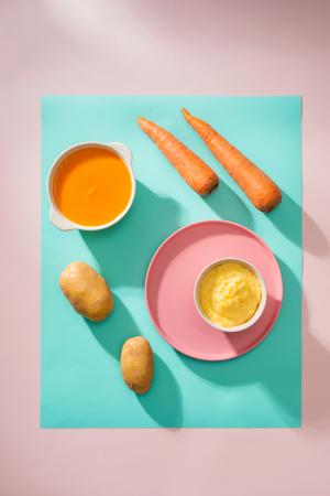 purea di bambino gialla e arancione in una ciotola isolata su sfondo colorato