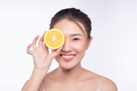 young and beautiful asian woman posing with a slice of orange on white background