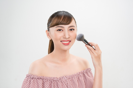 Beautiful smiling girl applying loose blush with cosmetic brush.