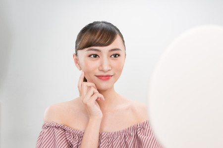 Beautiful smiling girl with natural makeup touching face. Stock Photo