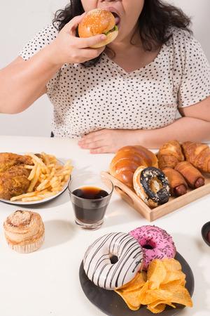 Curvy female preparing to eat hamburger, overeating problem, depression