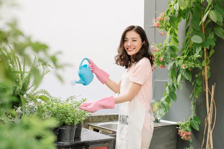 Chicas asiáticas riego azul en el jardín en el suelo