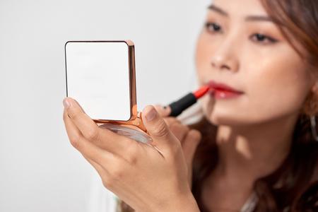 Atractiva mujer joven refrescando su lápiz labial de maquillaje sosteniendo una caja de polvo de espejo de mano en un día soleado Foto de archivo