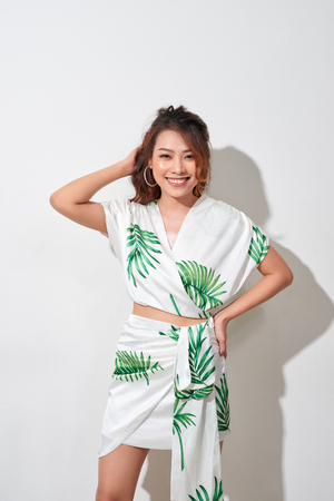 Beautiful young woman in tropical print green and white dress