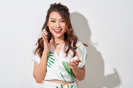 Hermosa chica asiática en vestido de verano haciendo maquillaje con su pequeño espejo y polvo en tarde soleada Foto de archivo
